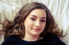 Chica joven hermosa que se relaja en el dormitorio Foto de archivo libre de regalías