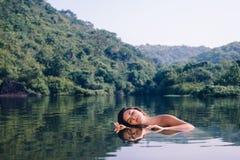 Chica joven hermosa que se relaja en el espejo del agua en un fondo de colinas verdes fotografía de archivo