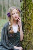 Chica joven hermosa que se sienta cerca de un árbol Fotografía de archivo libre de regalías