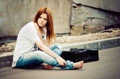 Chica joven hermosa que se sienta en el asfalto Imagenes de archivo