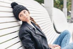 Chica joven hermosa que se sienta en el parque del banco Imagen de archivo libre de regalías