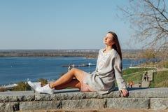 Chica joven hermosa que se sienta en el terrapl?n del r?o Volga imagen de archivo libre de regalías