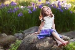 Chica joven hermosa que se sienta en roca en jardín fotografía de archivo
