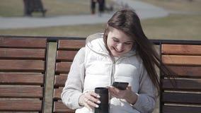 Chica joven hermosa que se sienta en un banco de madera en un parque de la ciudad en un café de consumición del traje blanco de u almacen de video