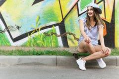 Chica joven hermosa que se sienta en un monopatín Copie el espacio Fotos de archivo