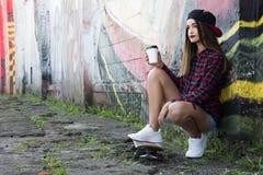 Chica joven hermosa que se sienta en un monopatín Copie el espacio Imagen de archivo
