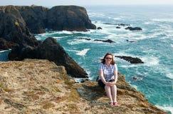 Chica joven hermosa que se sienta en una roca Imagenes de archivo
