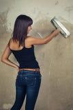 Chica joven hermosa que sostiene la espátula sobre grunge Imagen de archivo