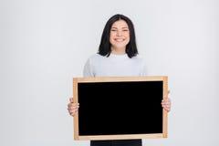 Chica joven hermosa que sostiene la pizarra en blanco Imagen de archivo libre de regalías