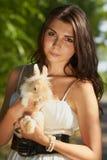 Chica joven hermosa que sostiene un conejito Imagen de archivo