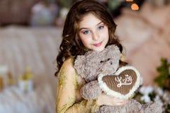 Chica joven hermosa que sostiene un oso de peluche en el fondo de t Imagenes de archivo
