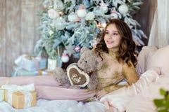 Chica joven hermosa que sostiene un oso de peluche y que sonríe contra el th Imagen de archivo libre de regalías
