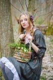 Chica joven hermosa que sostiene una cesta de flores Foto de archivo