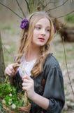 Chica joven hermosa que sostiene una cesta de flores y de lookin Imagenes de archivo