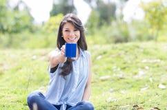 Chica joven hermosa que tiene una comida campestre Imagenes de archivo