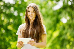 Chica joven hermosa que usa una tableta en un parque Fotografía de archivo