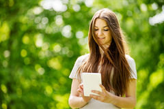 Chica joven hermosa que usa una tableta en un parque Fotos de archivo libres de regalías