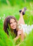 Chica joven hermosa sonriente feliz que miente entre hierba y flores Imagenes de archivo