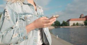 Chica joven irreconocible que manda un SMS en el teléfono en un parque de la ciudad Fotografía de archivo libre de regalías