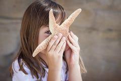 Chica joven juguetona que juega con las estrellas de mar Fotografía de archivo libre de regalías
