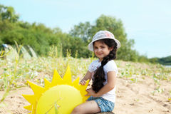 Chica joven juguetona que presenta con el sol de papel Imágenes de archivo libres de regalías