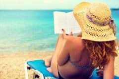 Chica joven, leyendo un libro en la playa Foto de archivo