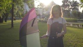 Chica joven linda con el paraguas multicolor que da vuelta y que mira a la cámara que sonríe en el parque Ocio del verano Joven metrajes