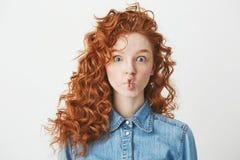 Chica joven linda con el pelo rizado astuto que hace la cara divertida sobre el fondo blanco Copie el espacio Fotografía de archivo libre de regalías