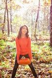 Chica joven linda con la calabaza en sus manos en parque del otoño Foto de archivo