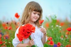 Chica joven linda con las amapolas en el campo del verano Foto de archivo