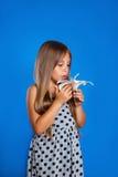 Chica joven linda con los ojos cerrados que huelen una flor Imagen de archivo libre de regalías