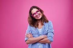 Chica joven linda en camisa y vidrios comprobados sobre rosa Fotografía de archivo