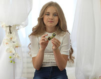 Chica joven linda en la camisa blanca con el pelo justo largo que juega con el hilandero verde de la persona agitada en sitio bri Fotos de archivo libres de regalías