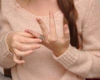 chica joven linda en un suéter que lleva a cabo un anillo en su finger foto de archivo libre de regalías