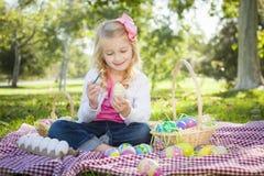 Chica joven linda que colorea sus huevos de Pascua con la brocha Foto de archivo