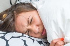 Chica joven linda que despierta en cama Imagenes de archivo