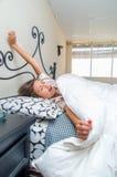 Chica joven linda que despierta en cama Fotografía de archivo