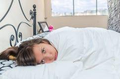 Chica joven linda que despierta en cama Imágenes de archivo libres de regalías