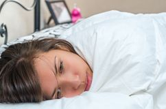 Chica joven linda que despierta en cama Imagen de archivo