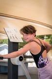 Chica joven linda que ejercita el cuerpo superior en la máquina del entrenamiento del gimnasio al aire libre Imagenes de archivo