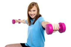 Chica joven linda que estira pesas de gimnasia de lado Fotos de archivo libres de regalías