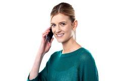Chica joven linda que habla en el teléfono móvil Imagen de archivo libre de regalías