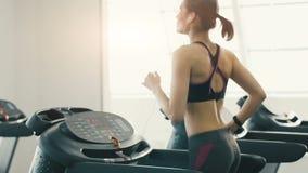 Chica joven linda que hace ejercicios en el bacground del gimnasio almacen de video