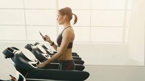Chica joven linda que hace ejercicios en el fondo del gimnasio almacen de video