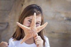 Chica joven linda que juega con las estrellas de mar Imagen de archivo libre de regalías