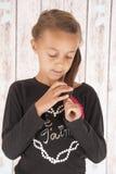 Chica joven linda que juega con su pelo que mira abajo Foto de archivo libre de regalías