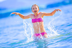 Chica joven linda que juega en el mar La muchacha pre-adolescente feliz disfruta del agua y de días de fiesta del verano en desti Fotos de archivo libres de regalías