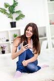 Chica joven linda que lee un SMS en móvil Fotografía de archivo