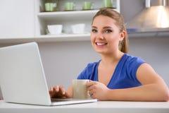 Chica joven linda que mecanografía en el ordenador portátil y el café de consumición Fotos de archivo