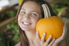 Chica joven linda que se divierte con las calabazas en el mercado Foto de archivo libre de regalías